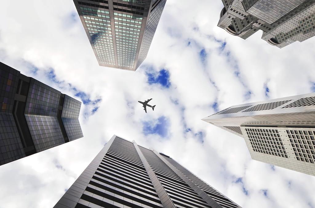 Airplane from below between houses.
